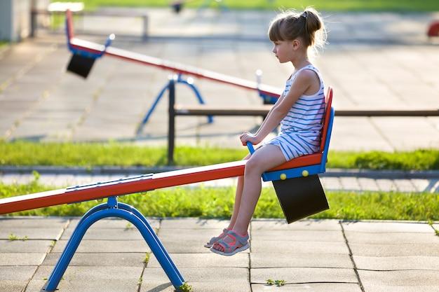 Leuk jong kindmeisje in openlucht op geschommelschommeling op zonnige de zomerdag.