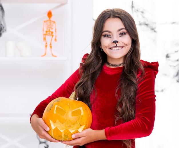 Leuk jong meisje die kwade halloween-pompoen houden