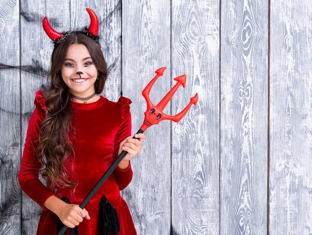 Leuk jong meisje gekleed in duivelskostuum