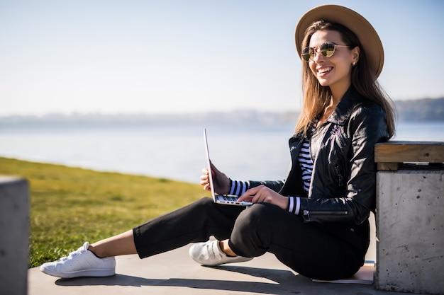 Leuk jong meisje gekleed in lederen jas stoel op de bank in de buurt van het pier meer