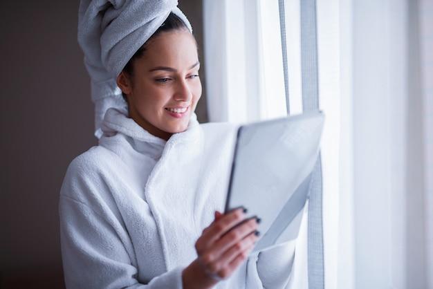 Leuk jong meisje in de tablet van de badjasholding en status voor het venster.