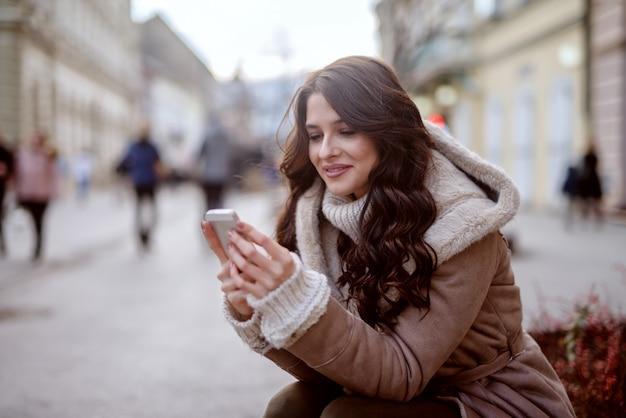 Leuk jong meisje in de winterjas die zich in straat bevindt en haar telefoon bekijkt. glimlachen en er gelukkig uitzien.