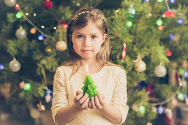 Leuk jong meisje in kerstmis met een kaars in haar handen