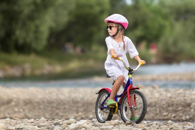 Leuk jong meisje in witte kleding, zonnebril met lange vlechten die roze berijdende het kindfiets van de veiligheidshelm dragen op kiezelsteenrivierbank op vage groene de zomerachtergrond. buitenshuis activiteit concept.