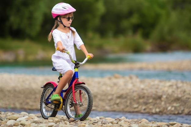 Leuk jong meisje in witte kleding, zonnebril met lange vlechten die roze veiligheidshelm berijdende kindfiets dragen op kiezelsteenrivieroever op de vage groene zomer. outdoors activiteit concept.