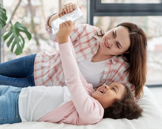 Leuk jong meisje kijken naar tekenfilms met moeder