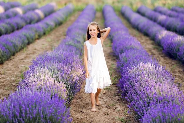 Leuk jong meisje loopt in een lavendelveld. ze draagt een witte zomerjurk.
