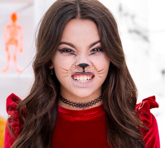 Leuk jong meisje met gezicht dat voor halloween wordt geschilderd