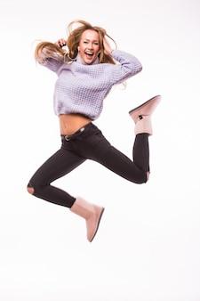 Leuk jong meisje met spijkerbroek en roze top energetisch geïsoleerd springen