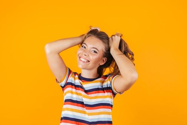 Leuk jong meisje poseren over gele muur ruimte haar in handen houden.