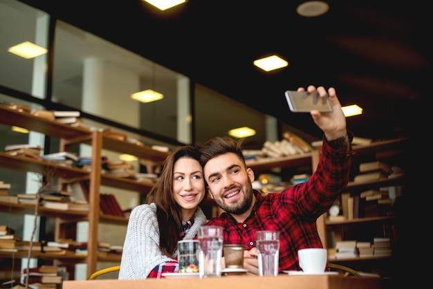 Leuk jong stel met datum in het moderne café, selfie te nemen