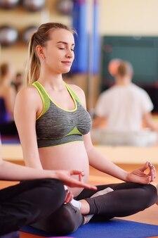Leuk jong zwanger meisje belast met fitness samen met een groep yoga in een sportclub