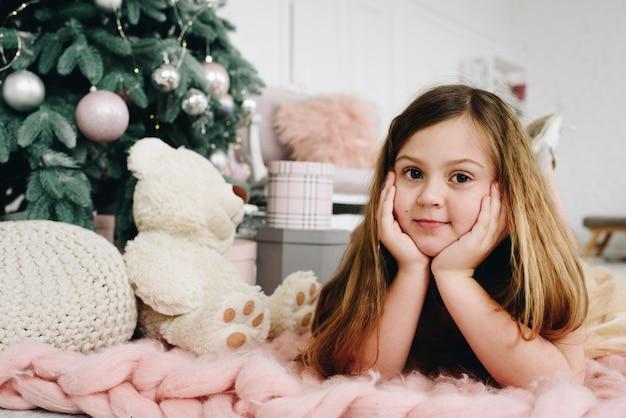 Leuk kaukasisch schoolmeisje dat dichtbij haar speelgoed en verfraaide kerstboom ligt
