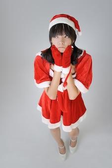 Leuk kerstmismeisje met grappige uitdrukking tegen grijze muur.