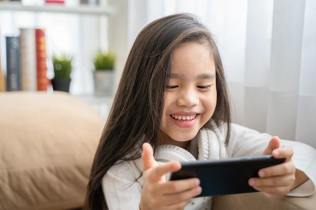Leuk kind gebruikend een smartphone en glimlachend terwijl thuis het zitten op bank