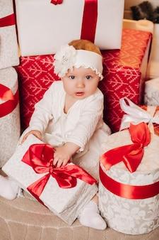 Leuk kind in het witte kleding stellen onder kerstmisboom.