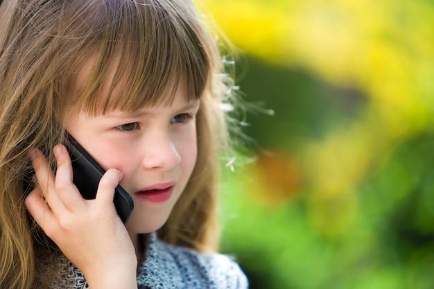 Leuk kind jong meisje dat op cellphone in openlucht spreekt. kinderen en moderne technologie, communicatie.