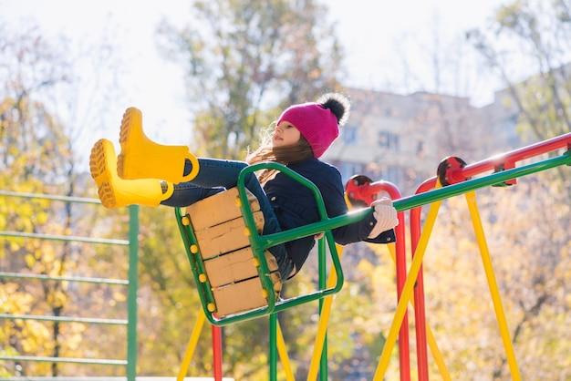 Leuk kind op speelplaats tijdens herfstwandeling