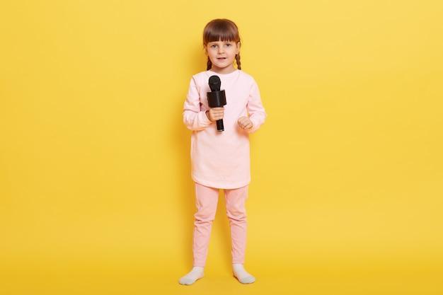 Leuk kind zingt met microfoon, kijkt direct naar de camera, draagt vrijetijdskleding, staand tegen gele muur, kind met staartjes die in karaoke presteren.