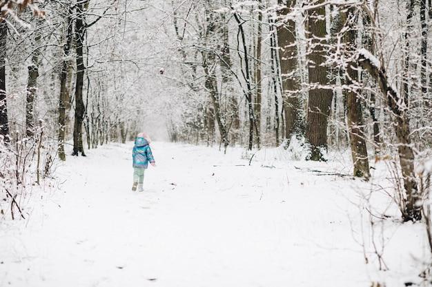 Leuk kindmeisje in een kleurrijke kleding die in een sneeuwwinterpark loopt
