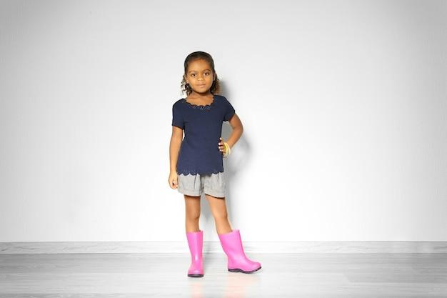 Leuk klein afrikaans amerikaans meisje in rubberen laarzen tegen lichte muur. mode concept