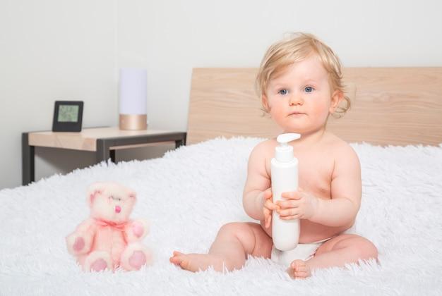 Leuk klein babymeisje met fles babyolie in ouderslaapkamer.