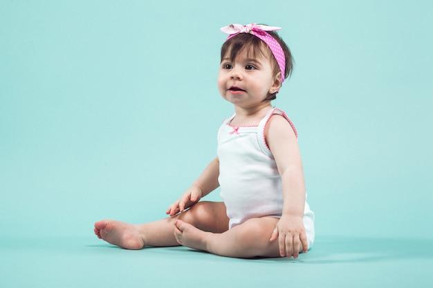 Leuk klein glimlachend meisje met roze boog in haarzitting in studio die blauw stellen