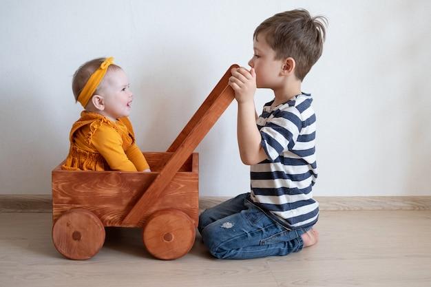 Leuk klein kaukasisch babymeisje en peuterjongen die met houten kar spelen. broers en zussen. broer en zus.