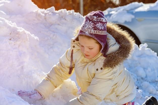 Leuk klein kaukasisch meisje dat in de wintersneeuw op een kind speelt