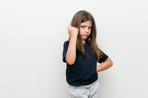 Leuk klein kaukasisch meisje dat vuist toont aan camera, agressieve gelaatsuitdrukking.