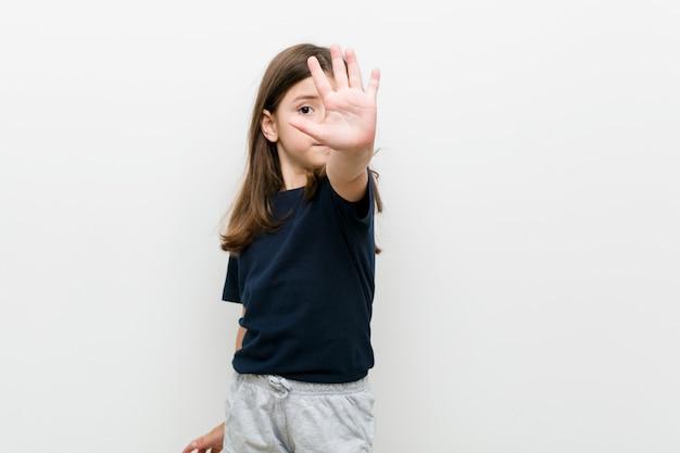 Leuk klein kaukasisch meisje dat zich met uitgestrekte hand bevindt die stopbord toont, dat u verhindert.