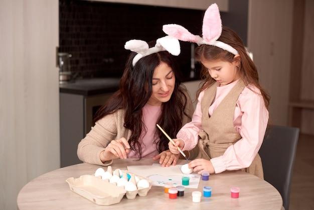 Leuk klein kindmeisje dat konijntjesoren draagt op paasdag