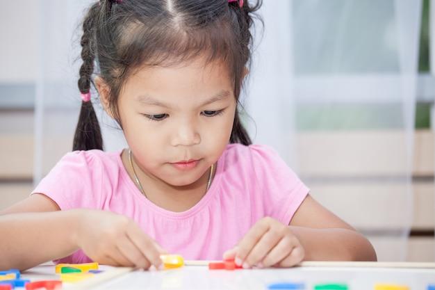 Leuk klein kindmeisje dat pret heeft om magnetische alfabetten aan boord in de ruimte te spelen en te leren
