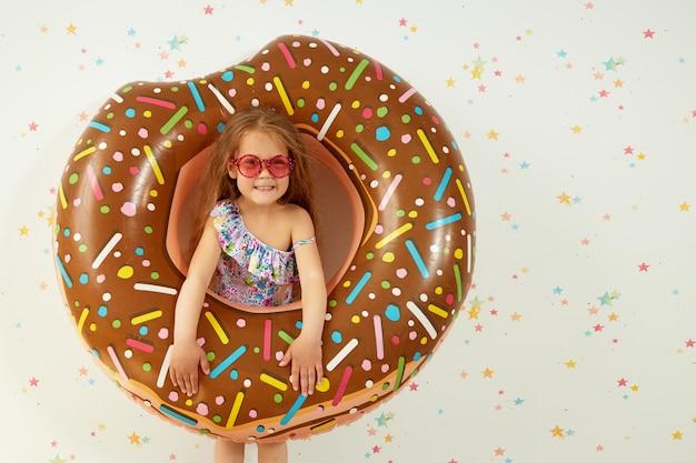 Leuk klein kindmeisje in hoed met opblaasbare ring op kleurenmuur. zomervakantie thuis in quarantaine plaatsen