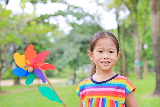 Leuk klein kindmeisje met windturbine in de tuin