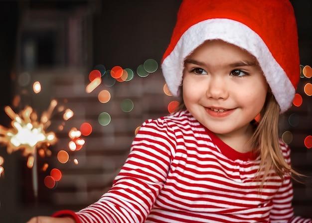Leuk klein meisje dat in kerstmanhoed brandend sterretje houdt en gelukkig glimlacht