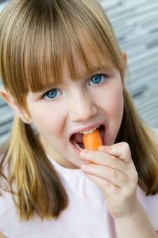 Leuk klein meisje eet wortel en kijkt naar de camera