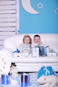 Leuk klein meisje en jongen die met giftdozen op een witte bank zitten. kerstmis en nieuwjaar vieren.