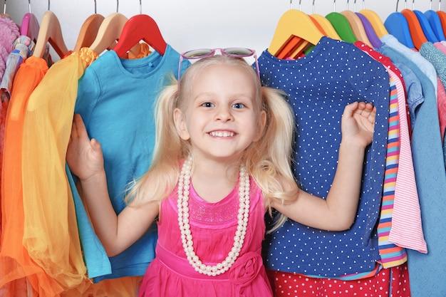 Leuk klein meisje in kleerkast met kleren