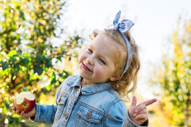 Leuk klein meisjeskind dat rijpe organische rode appel eet in de appelboomgaard in de herfst.