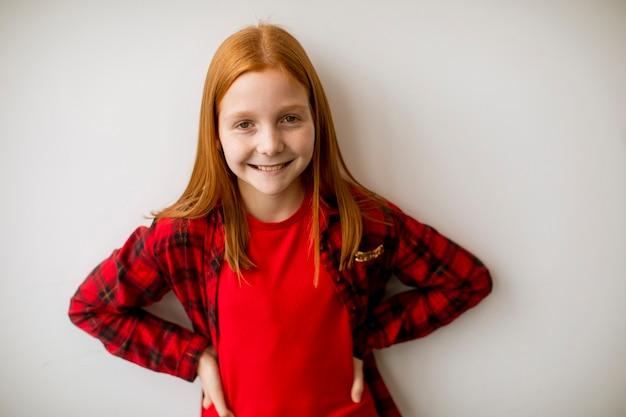 Leuk klein rood haarmeisje dat zich bij de witte muur bevindt