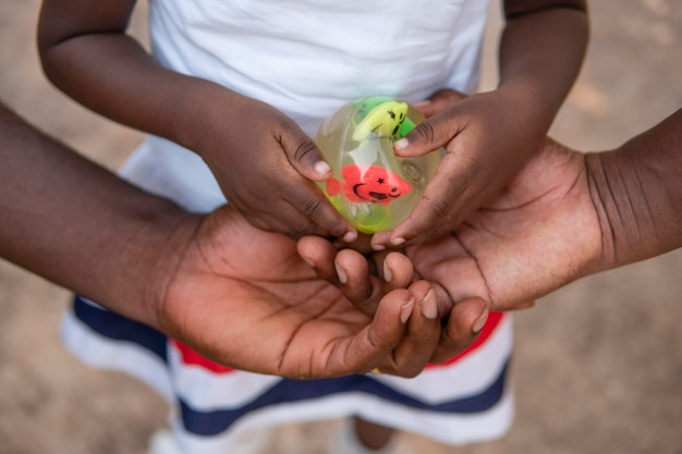 Leuk klein zwart meisje dat een stuk speelgoed met vissen houdt
