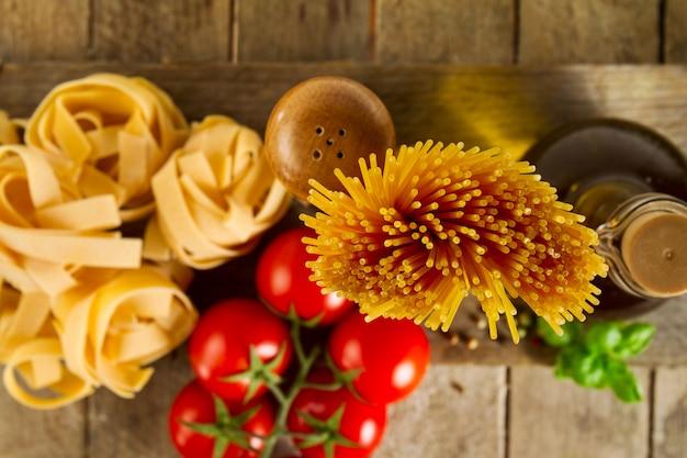 Leuk kleurrijk vers italiaans voedselconcept met verschillende pastaspaghetti, vers basil, tomaten, specerijen. kookconcept. plaats voor tekst. detailopname.