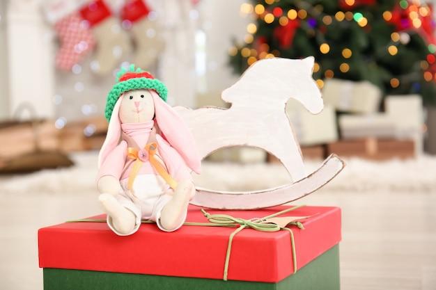 Leuk konijntjesstuk speelgoed en houten paard op giftdoos tegen onscherpe achtergrond