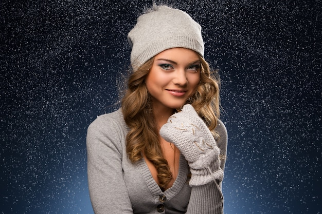 Leuk krullend meisje dat vuisthandschoenen draagt tijdens sneeuwval