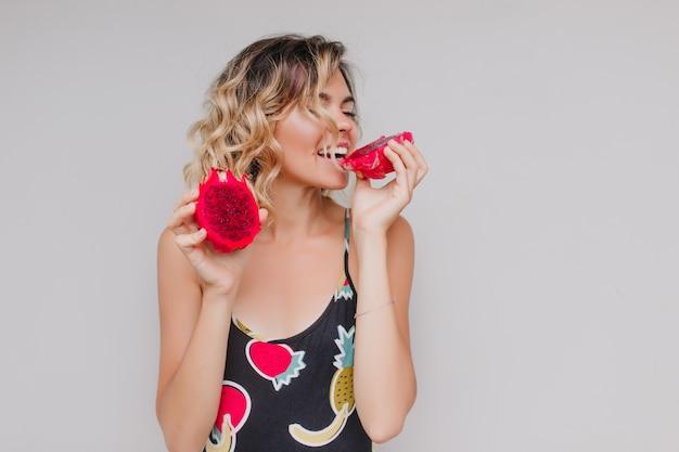 Leuk krullend meisje pitaya eten met plezier. binnenfoto van blonde blanke vrouw die van exotisch fruit geniet.