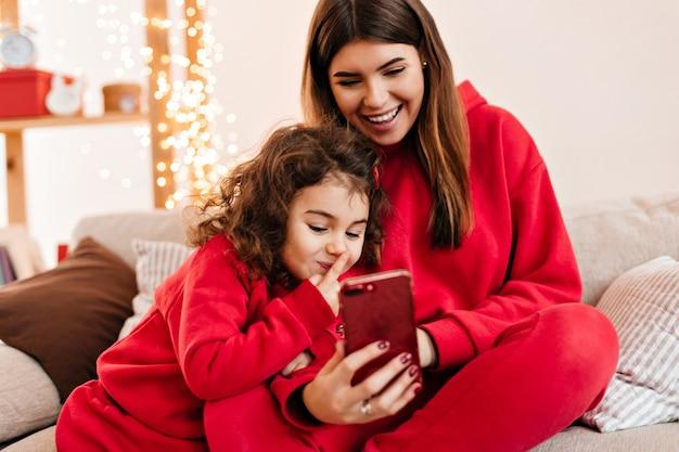 Leuk krullend meisje smartphone met moeder. glimlachende jonge moeder koelen met preteen dochter op de bank.