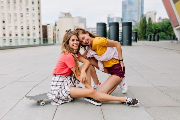 Leuk lachend blond meisje met lange benen zittend op skateboard in de buurt van haar brunette zus in geel overhemd