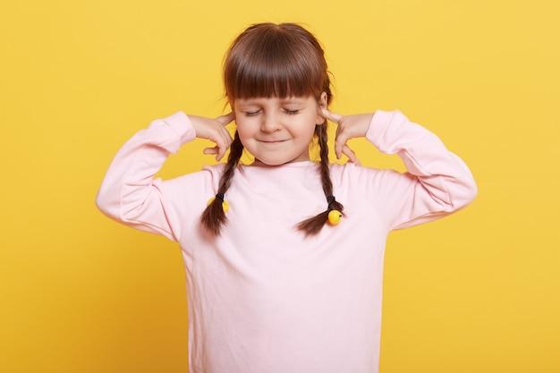 Leuk leuk jong geitjemeisje die oren met vingers bedekken, ogen gesloten houden en glimlachen, niet willen horen, vrijetijdskleding dragen, geïsoleerd over gele achtergrond staan.