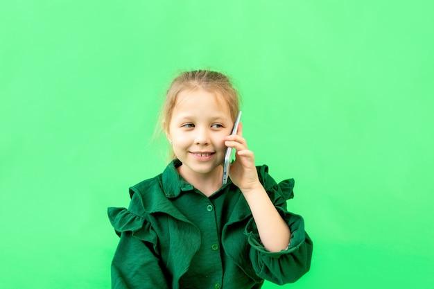 Leuk meisje 7-9 jaar oud praten aan de telefoon op groen